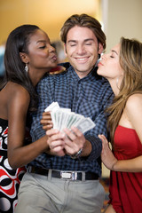 happy man winning money in a casino with two girls kissing him