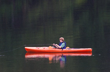 A young teenage boy fishing from a kayak in the evening