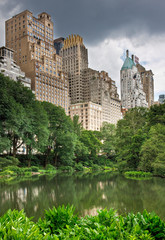 A pond in central park with buildings behind it in New York City