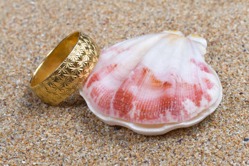 Seashell and a gold ring in the sand
