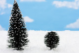 Two evergreen trees on snow with snowflake background poster