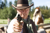 Cowboy aiming gun, focus only on gunpoint, horwe in background poster