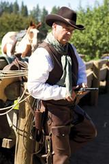 Handsome older cowboy leaning against a fence