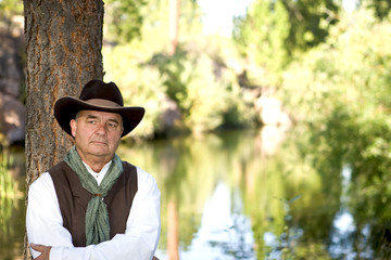 Handsome older cowboy leaning against a tree