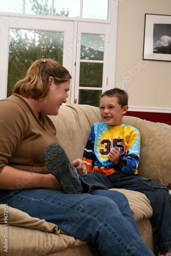 mother and son on couch lauging together