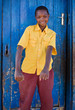african boy with yellow shirt, in a village