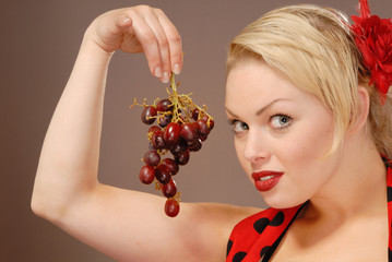 pretty girl holding red grapes to tempt you