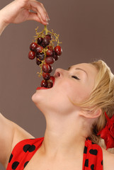 pretty girl holding up red grapes and tasting them