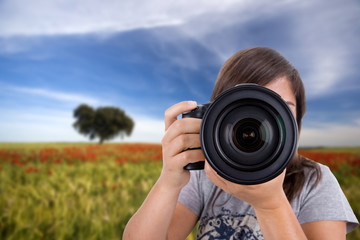 young woman with landscape as background taking photos