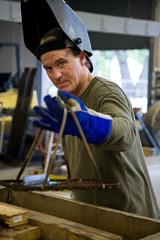 Metal worker in a factory wearing his welding visor.