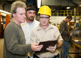 Factory workers and foreman discuss inspection report