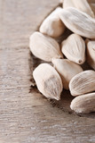white cardamom pods on old wood, macro, shallow DOF poster