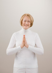 Studio shot of senior woman in white praying with hands clasped