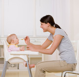 Fototapety Mother feeding hungry baby in highchair in kitchen