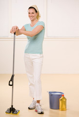 Satisfied woman posing with mop and floor cleaner at home