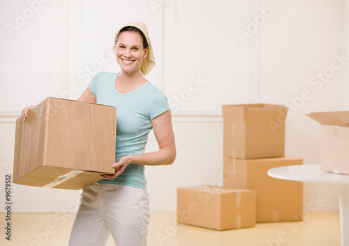 Woman moving cardboard boxes in new home