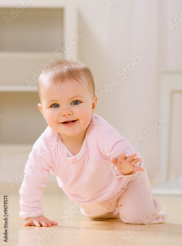 Close up of smiling baby crawling on livingroom floor