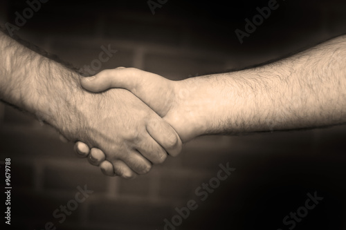Two business men shaking hand in sepia tone.