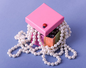 small pink box with white pearl beads