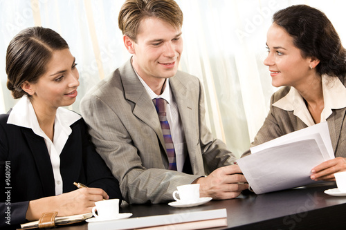 Photo of friendly man and woman sitting in office