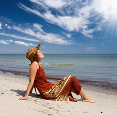 Girl in dress become sunburnt at sand sea coast