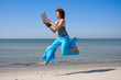 Girl running along beach and looking to laptop