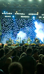 Concert stage lights out of focus and people crowd in blur