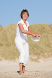 Active senior woman is tossing a frisbee at the beach poster