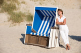 Active senior woman with white clothes at a beachchair. poster