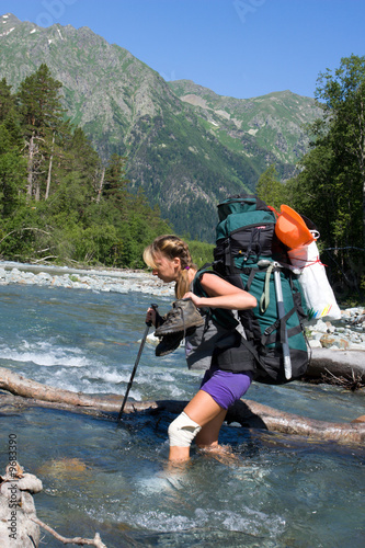 Backpacker girl moving across the mountain river