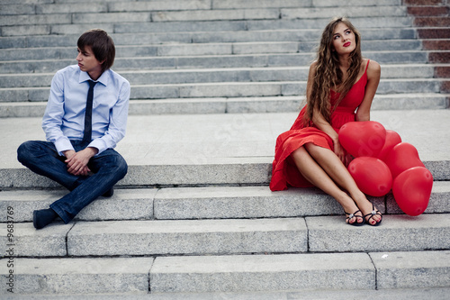 Romantic teenager couple in quarrel sitting on staircase