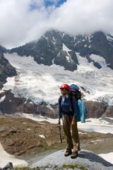Backpacker girl in helmet standing on big stone