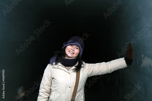 Asian woman having fun inside an ice tunnel during winter.