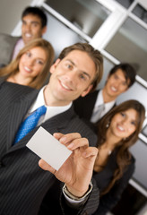 businessman showing his business card with a group