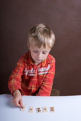 The little boy displays on a table of a card with figures