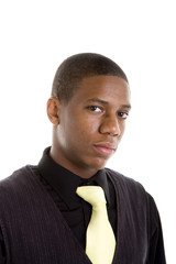 A young black man in a yellow tie, looking at camera