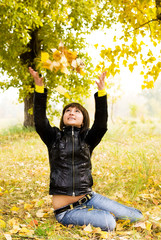 pretty brunette girl playing with yellow leaves in the park