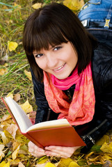 beautiful smiling girl with a book in the park