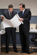 Businessmen collaborating over blueprints in cubicle