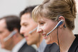 Happy co-workers in headsets working in call center