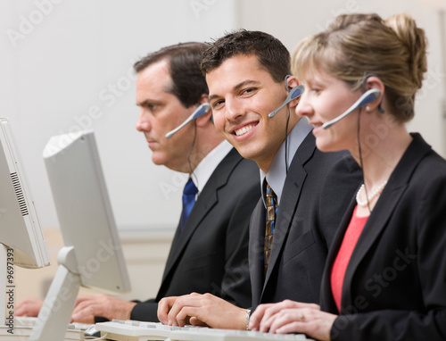 Co-workers in headsets working at computers in call center