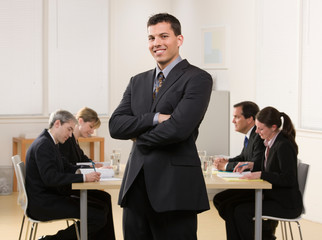 Confident businessman with co-workers in conference room