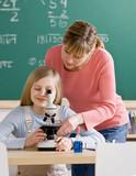 Teacher helping student adjust microscope in classroom
