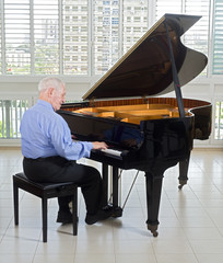 senior man playing on a grand piano at home