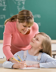 Teacher explaining homework to student in school classroom