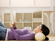 Relaxed woman laying on floor enjoying reading a book
