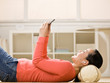 Woman listening to music on mp3 player while laying on floor