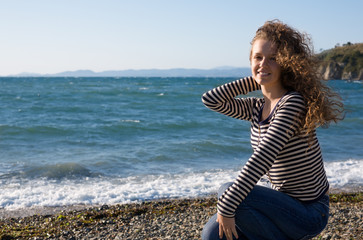 Girl enjoys freshness of the sea in beams of the leaving sun.