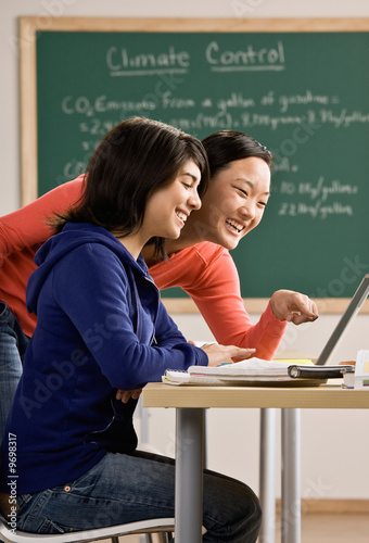 Student with laptop doing homework with friend in classroom