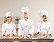 Chef co-workers in toques kneading dough in commercial kitchen